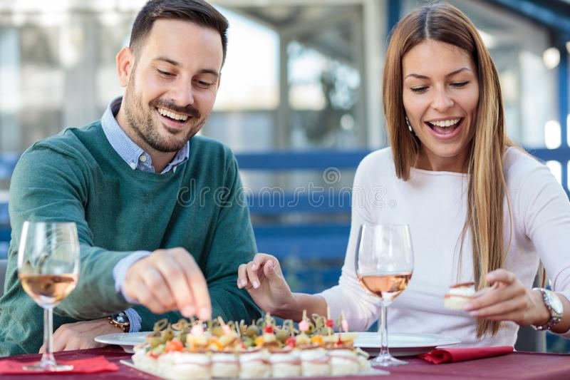 Pares jovenes felices que gozan de los aperitivos y que beben el vino rosado antes del almuerzo imagen de archivo