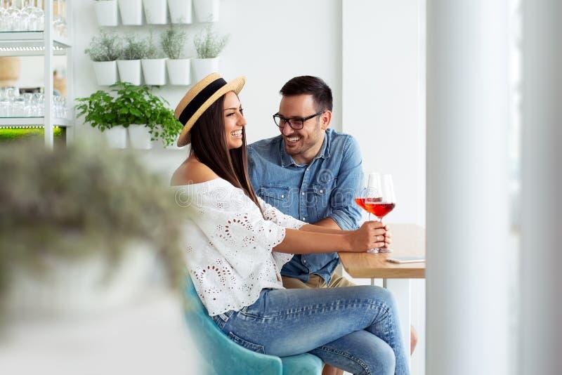 Pares jovenes felices que gozan de un vidrio de vino tinto después de hacer compras foto de archivo