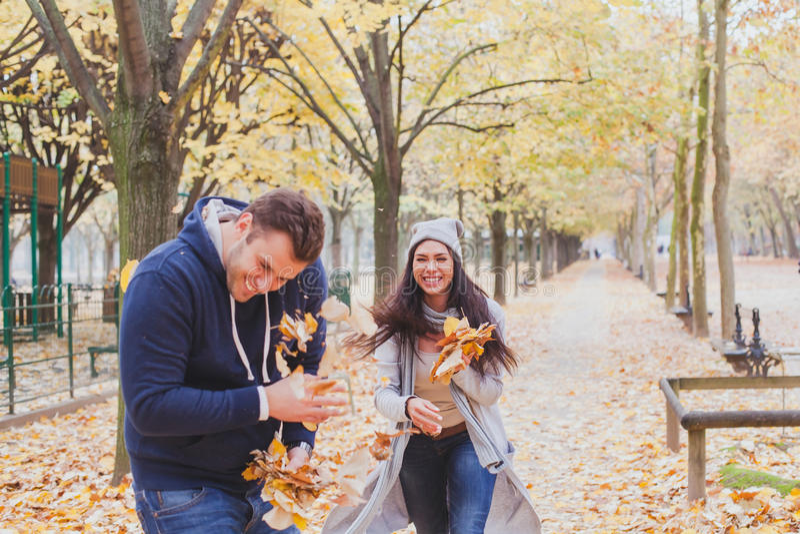 Pares jovenes felices que juegan afuera en parque del otoño foto de archivo libre de regalías