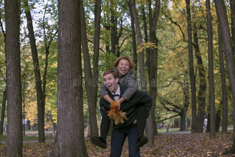 Pares jovenes felices que juegan con las hojas caidas en parque del otoño imágenes de archivo libres de regalías