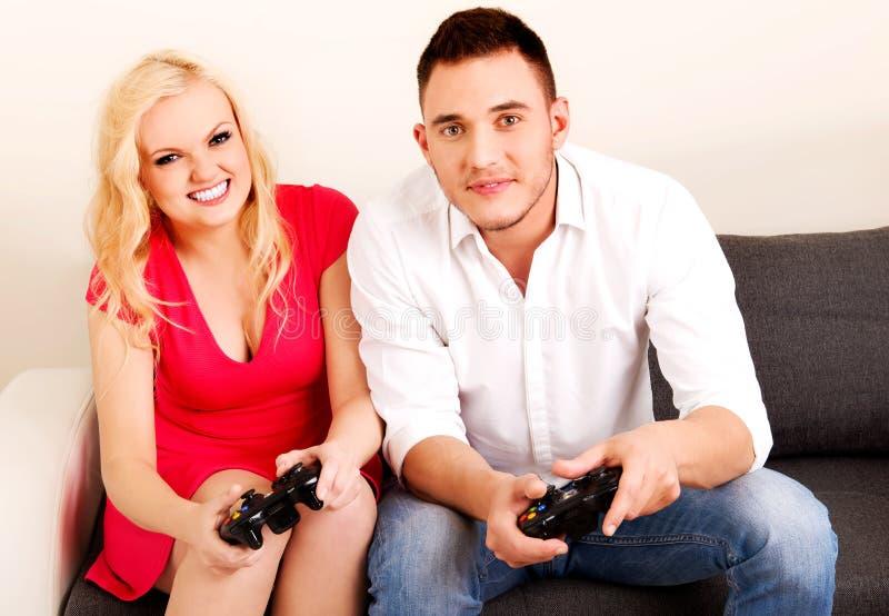 Pares jovenes felices que juegan a los juegos video fotos de archivo libres de regalías