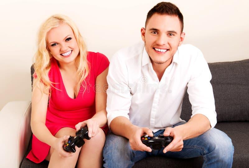 Pares jovenes felices que juegan a los juegos video imagenes de archivo