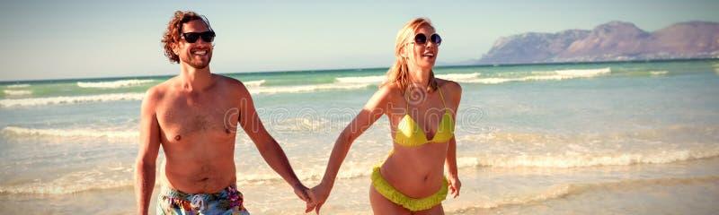 Pares jovenes felices que llevan a cabo las manos mientras que corre en la playa imagen de archivo libre de regalías