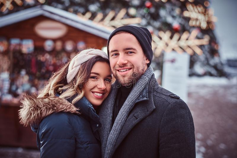 Pares jovenes felices que llevan la ropa caliente que se coloca cerca de un árbol de navidad de la ciudad, gozando pasando el tie fotografía de archivo libre de regalías