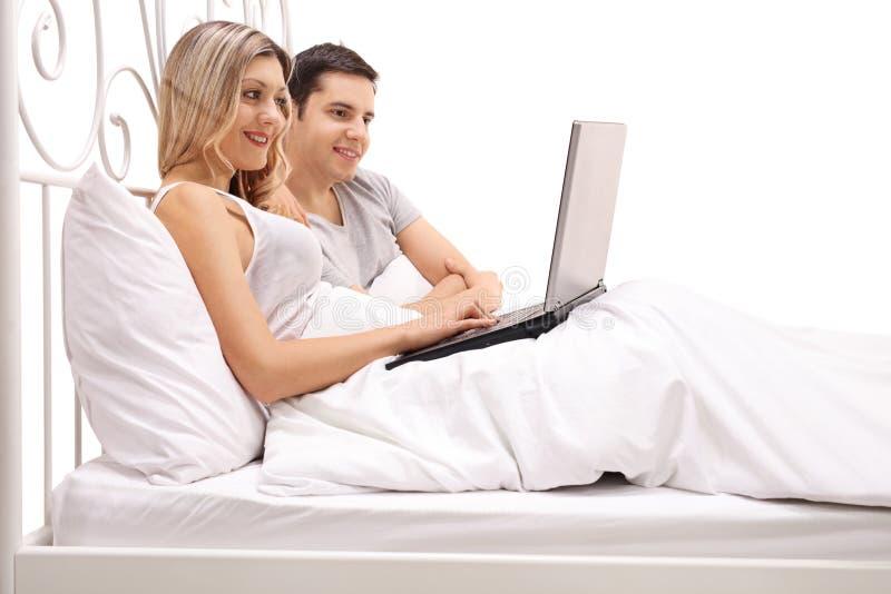 Pares jovenes felices que mienten en cama y que miran un ordenador portátil imagenes de archivo