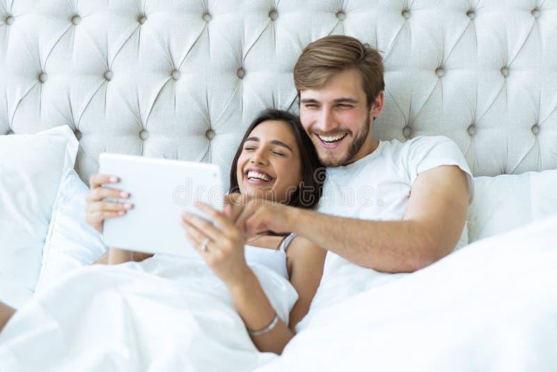 Pares jovenes felices que mienten en la cama en un dormitorio y que usan la tableta digital foto de archivo