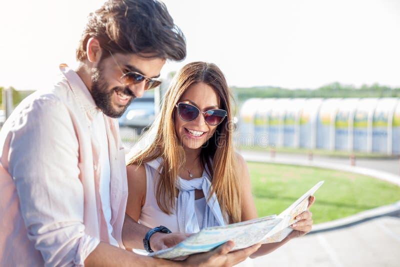 Pares jovenes felices que miran el mapa de la ciudad, viajando al extranjero foto de archivo libre de regalías