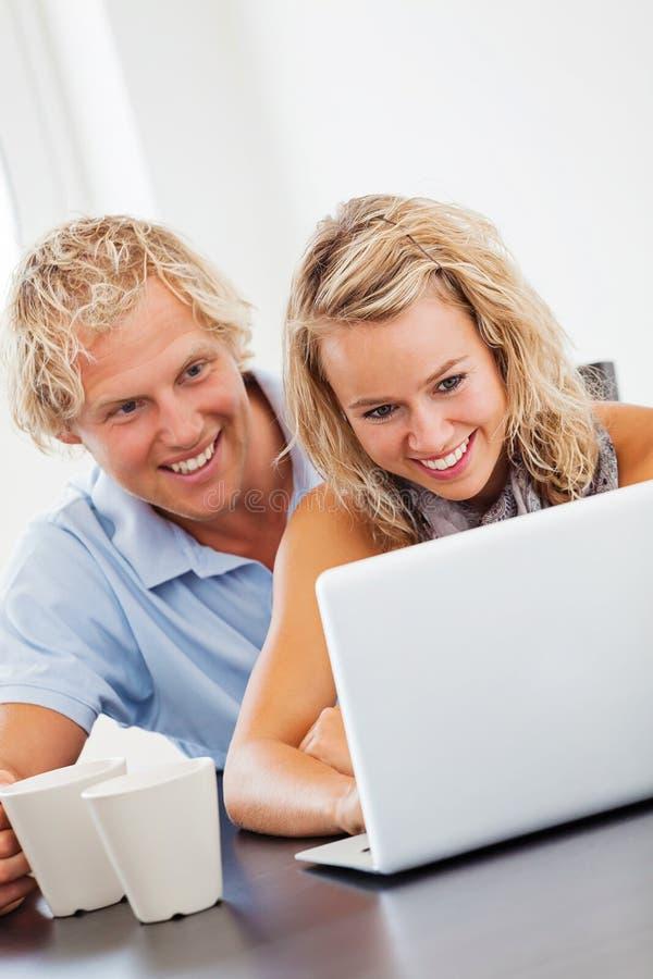 Pares jovenes felices que miran la computadora portátil foto de archivo libre de regalías