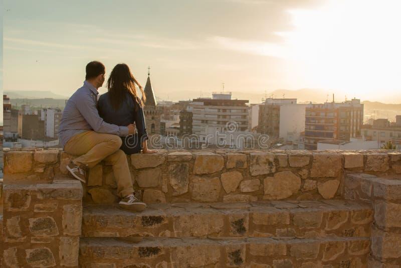 Pares jovenes felices que miran las opiniones en la ciudad la puesta del sol fotos de archivo libres de regalías