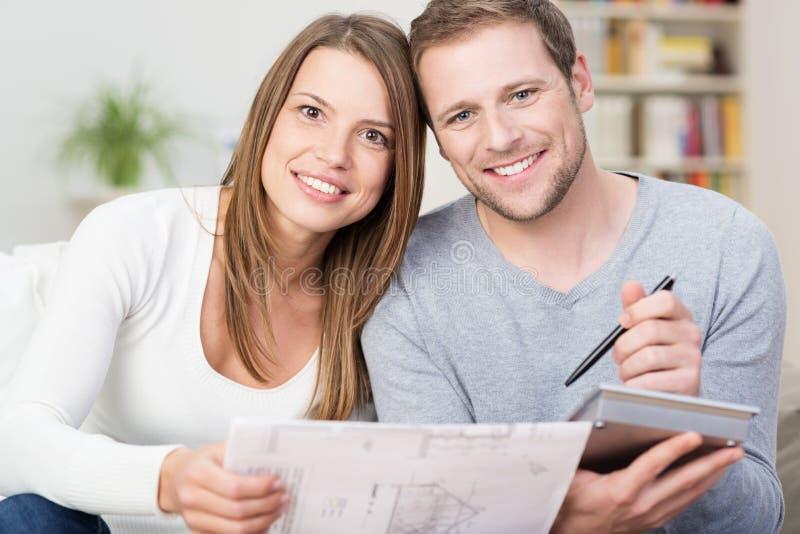 Pares jovenes felices que miran un diagrama fotos de archivo libres de regalías