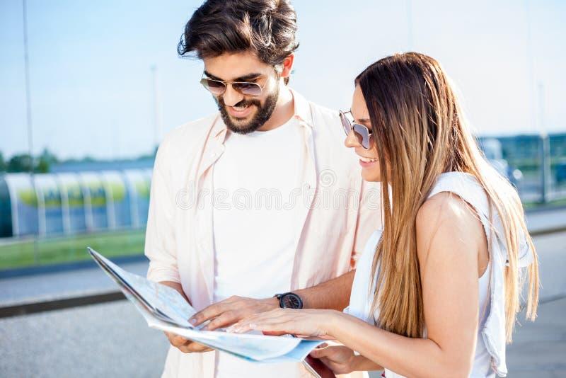 Pares jovenes felices que miran un mapa y que buscan para las direcciones imagen de archivo libre de regalías