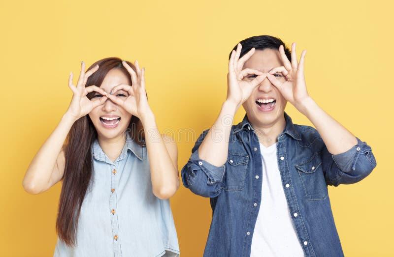 Pares jovenes felices que muestran el gesto de mirada imágenes de archivo libres de regalías