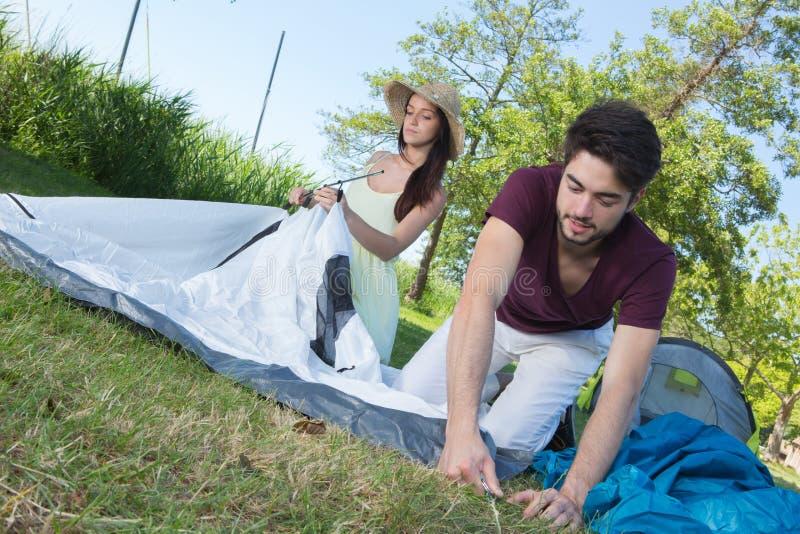 Pares jovenes felices que ponen su tienda en el camping fotos de archivo
