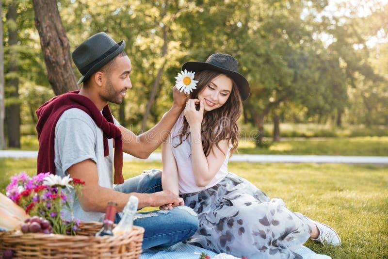 Pares jovenes felices que relajan y que tienen comida campestre en parque imagenes de archivo