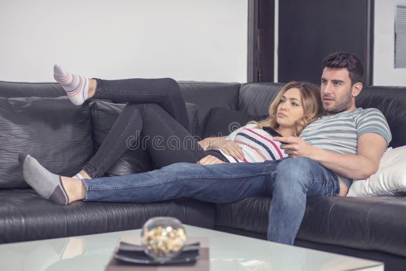 Pares jovenes felices que relajan y que ven la TV en casa imagenes de archivo