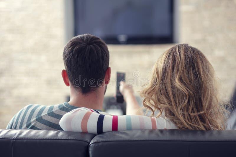 Pares jovenes felices que relajan y que ven la TV en casa fotos de archivo libres de regalías