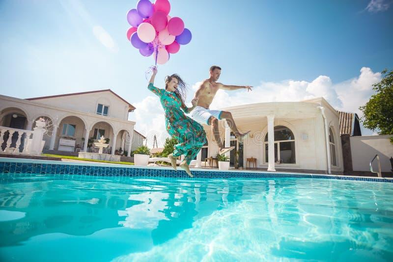 Pares jovenes felices que saltan en la piscina imagenes de archivo