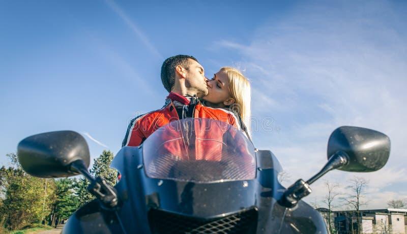 Pares jovenes felices que se besan en la motocicleta imagen de archivo libre de regalías