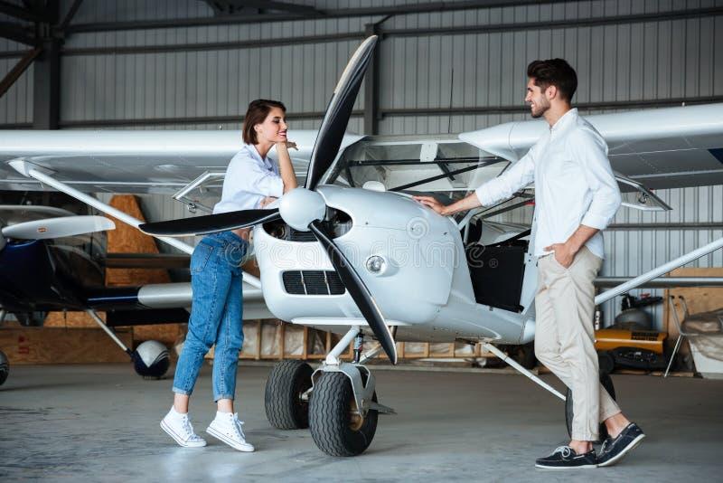 Pares jovenes felices que se colocan cerca del pequeño avión imágenes de archivo libres de regalías