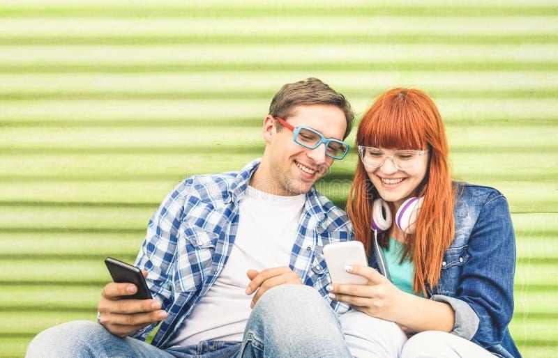 Pares jovenes felices que se divierten con el teléfono elegante móvil en el vintage imagen de archivo