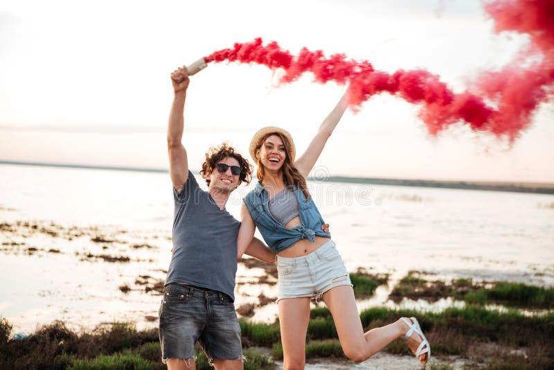 Pares jovenes felices que se divierten con la bomba de humo a disposición fotografía de archivo