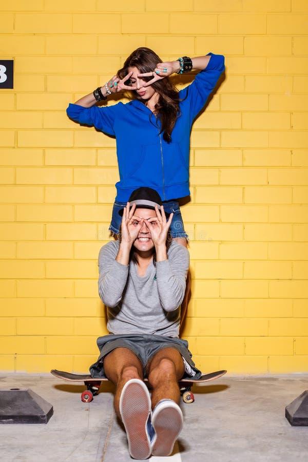 Pares jovenes felices que se divierten delante de la pared de ladrillo amarilla fotos de archivo