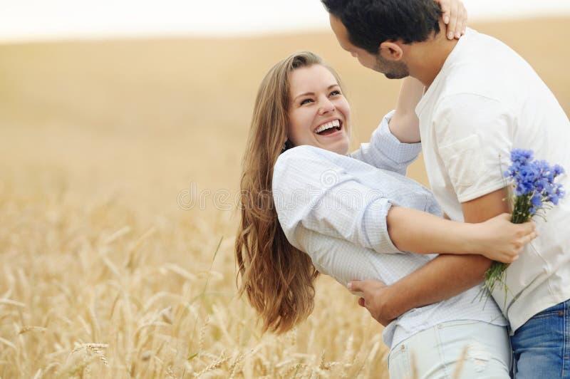 Pares jovenes felices que se divierten en campo del verano imagenes de archivo