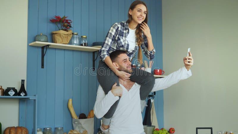Pares jovenes felices que se divierten en cocina en casa La muchacha se está sentando en cuello del ` s del novio mientras que él imagenes de archivo
