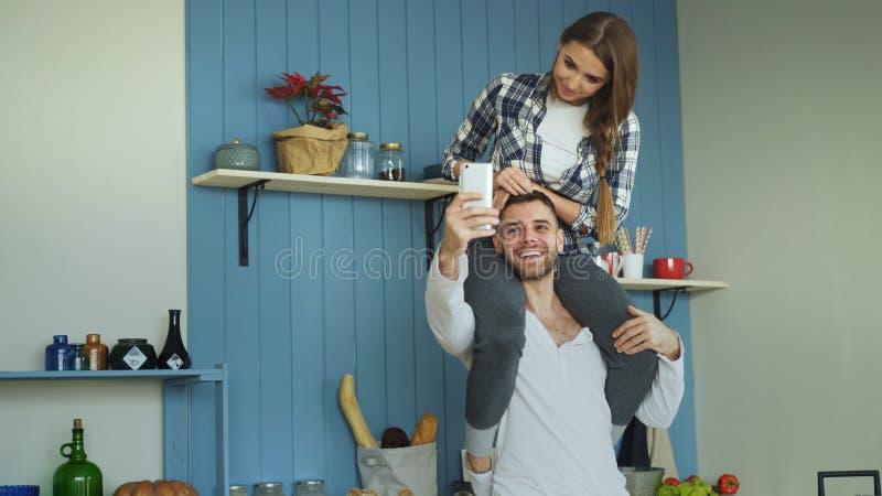 Pares jovenes felices que se divierten en cocina en casa La muchacha se está sentando en cuello del ` s del novio mientras que él fotografía de archivo