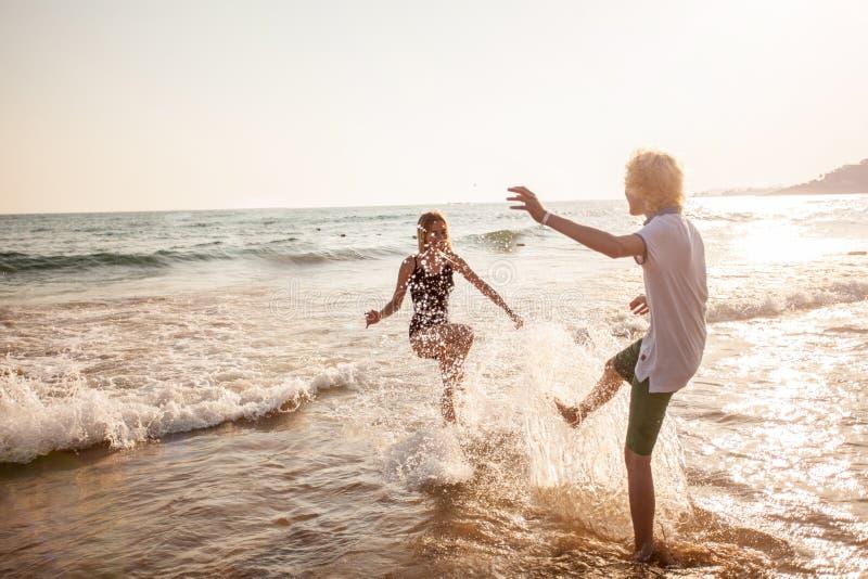 Pares jovenes felices que se divierten en la playa el d?a soleado imagenes de archivo