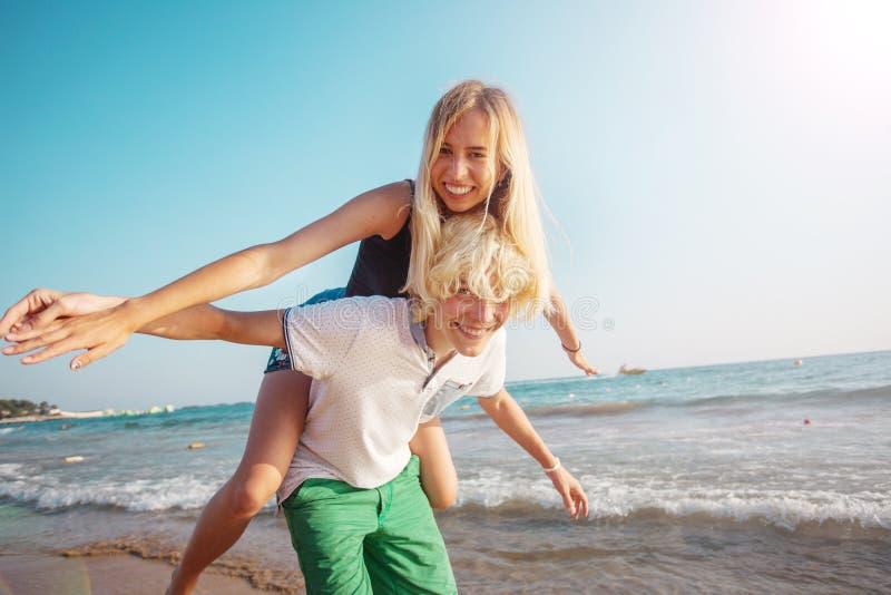 Pares jovenes felices que se divierten en la playa el d?a soleado imágenes de archivo libres de regalías