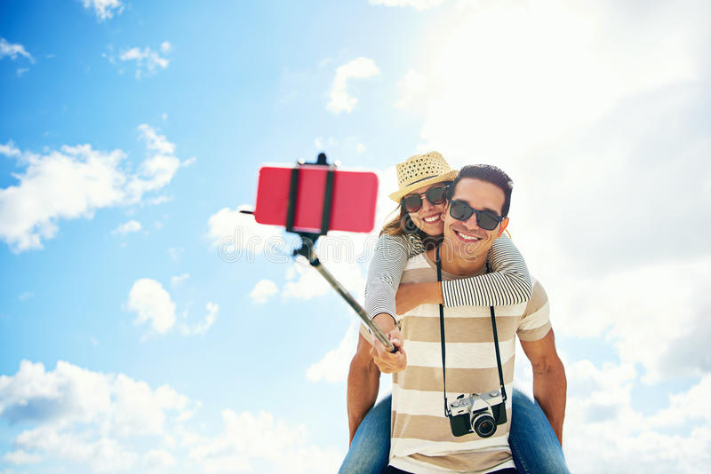 Pares jovenes felices que se divierten que toma un selfie imagen de archivo libre de regalías