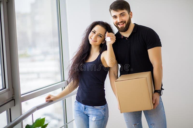 Pares jovenes felices que se mueven en el nuevo hogar que desempaqueta las cajas foto de archivo