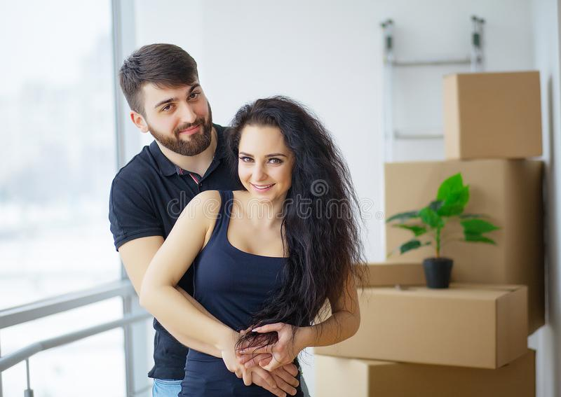 Pares jovenes felices que se mueven en el nuevo hogar que desempaqueta las cajas fotos de archivo