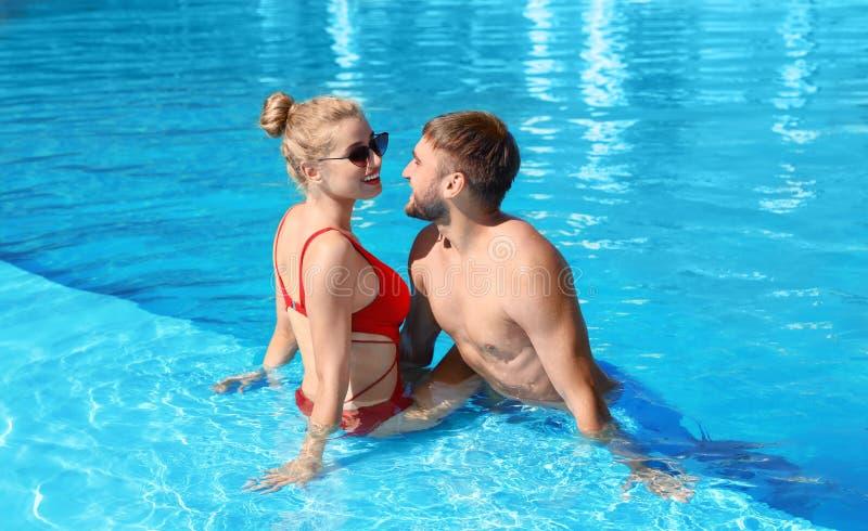 Pares jovenes felices que se relajan en piscina foto de archivo