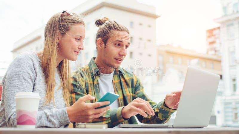 Pares jovenes felices que se sientan en café con el ordenador portátil y que discuten planes juntos, hombre sorprendido que mira  foto de archivo