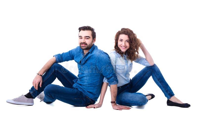 Pares jovenes felices que se sientan en el piso aislado en blanco imagen de archivo libre de regalías