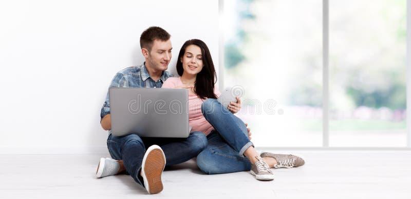 Pares jovenes felices que se sientan en el piso con un ordenador portátil que busca su nuevos hogar y muebles Mofa para arriba imágenes de archivo libres de regalías