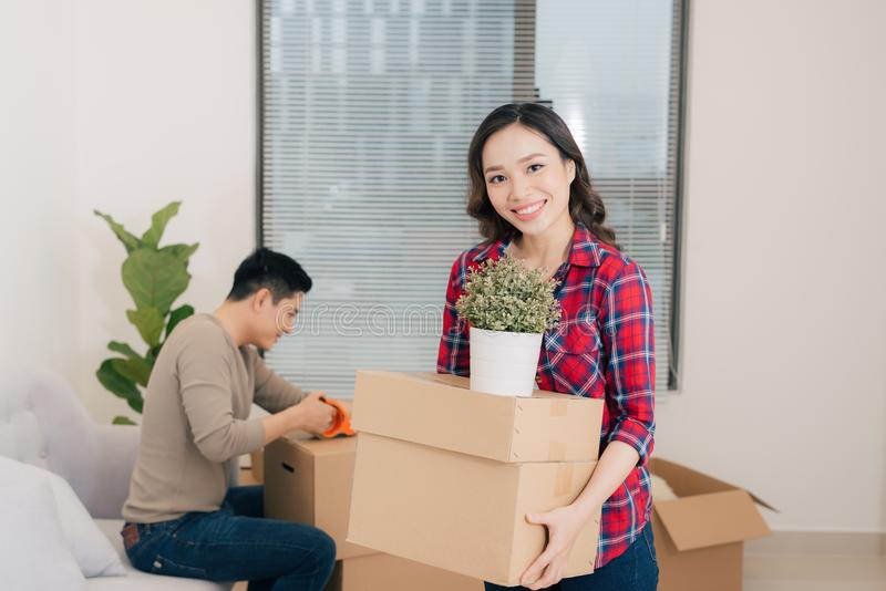Pares jovenes felices que se trasladan al nuevo apartamento con el boxe de empaquetado foto de archivo libre de regalías