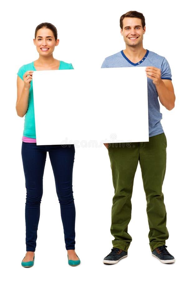 Pares jovenes felices que sostienen la cartelera foto de archivo libre de regalías