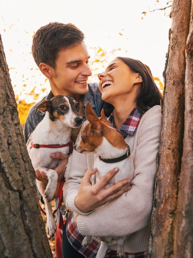 Pares jovenes felices que sostienen perros en parque y la sonrisa fotos de archivo libres de regalías