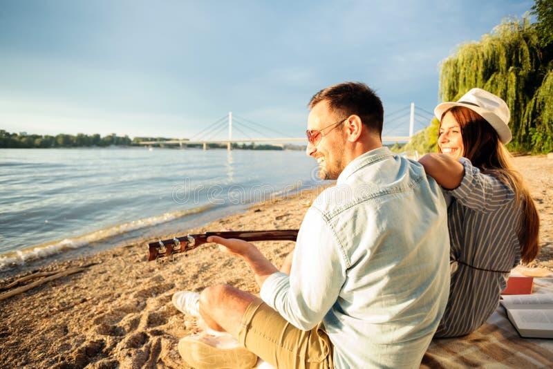 Pares jovenes felices que tienen un gran rato junto en la playa, tocando la guitarra fotos de archivo