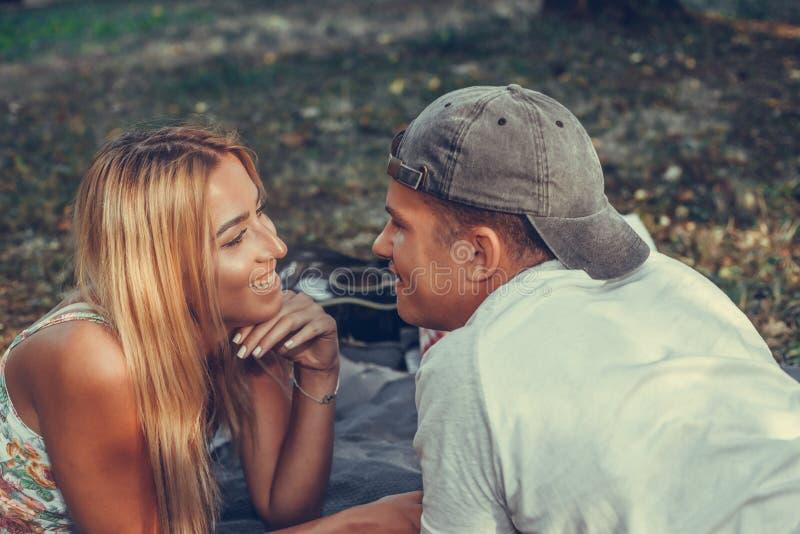 Pares jovenes felices que tienen una comida campestre en el parque en un día soleado imagenes de archivo