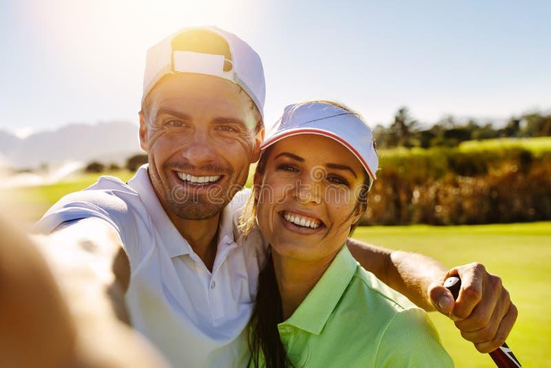 Pares jovenes felices que toman el selfie en el campo de golf foto de archivo