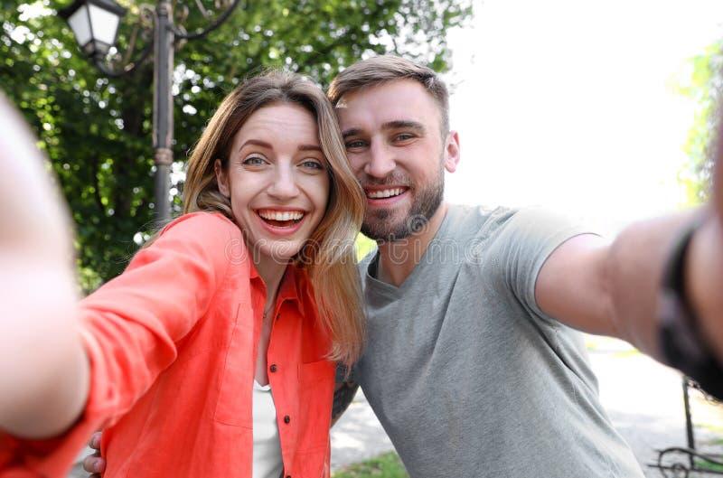 Pares jovenes felices que toman el selfie imagen de archivo libre de regalías