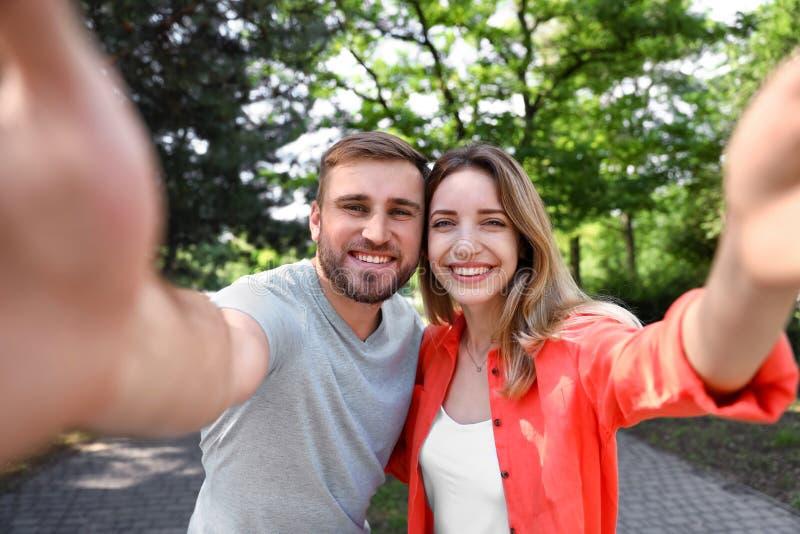 Pares jovenes felices que toman el selfie imagenes de archivo