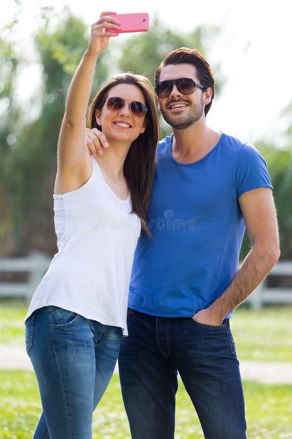Pares jovenes felices que toman selfies con su smartphone en el par fotografía de archivo libre de regalías