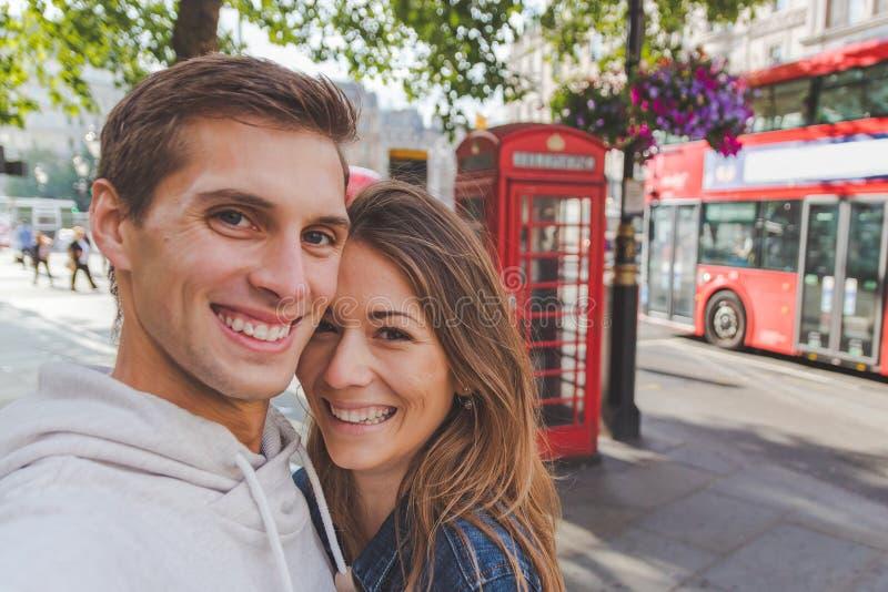 Pares jovenes felices que toman un selfie delante de una caja del teléfono y de un autobús rojo en Londres foto de archivo