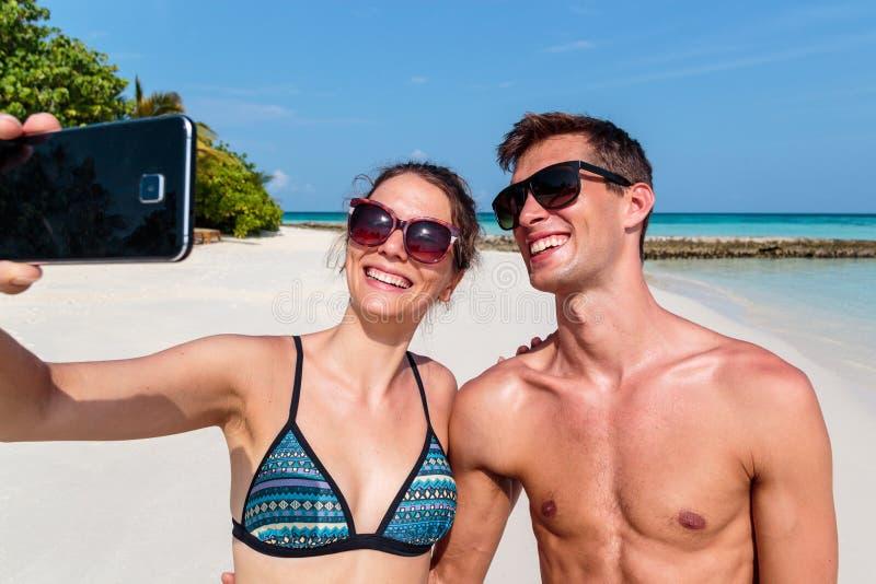 Pares jovenes felices que toman un selfie Isla tropical como fondo fotografía de archivo libre de regalías