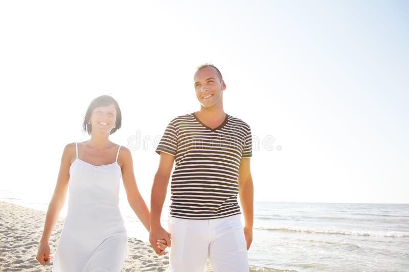 Pares jovenes felices que toman una caminata en la playa. imagenes de archivo